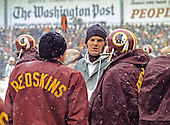 Washington Redskins back-up quarterback Sam Wyche (18), center, discusses strategy with fellow quarterbacks Sonny Jurgensen (9), left, and Billy Kilmer (17), right, on the sidelines during the game against the Philadelphia Eagles at RFK Stadium in Washington, DC on Sunday, December 16, 1973.  The Redskins won the game 38 - 20 to end their regular season with ten wins and four losses to qualify for the NFC play-offs.<br /> Credit: Arnie Sachs / CNP