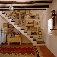 A collection of prints in gilt and silver gilt bamboo frames lines the walls of this open staircase