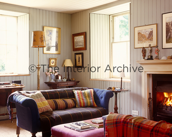 Brightly coloured plaid blankets have been used to cover the sofas in this cosy living room
