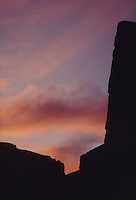 Stock photo of desert cliffs outlined in black silhouette by a sunset sky.
