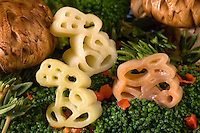Pasta in bunny shape on a bed of fresh broccoli with portabella mushrooms,rosemarine and red peppers