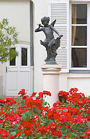 In the court yard at Champagne Deutz a statue on a pedestal of young Cupid in a sea of red flowers It has given the name to Deutz' champagne cuvee Amour de Deutz at Champagne Deutz in Ay, Vallee de la Marne, Champagne, Marne, Ardennes, France