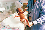 nurse holding premature infant in neonatal intensive care unit