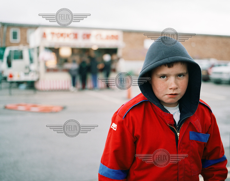"A boy dressed in overalls makes his way into Wimbledon Stadium to watch the first banger race of the day after having chips from the fast food stall ""A Touch of Class"" at Wimbledon Stadium in London. Banger racing is practiced by small communities throughout the country. They invest all their time and money in doing up old cars, only to smash them to pieces by the end of the week. They've been doing it for generations. Whether as a driver or spectator, the ritual satisfies a common human urge: to create and to destroy..."
