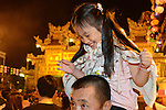 Donggang, Taiwan -- Father and daughter having fun before the boat burning ceremony. Well, at least the daughter does!