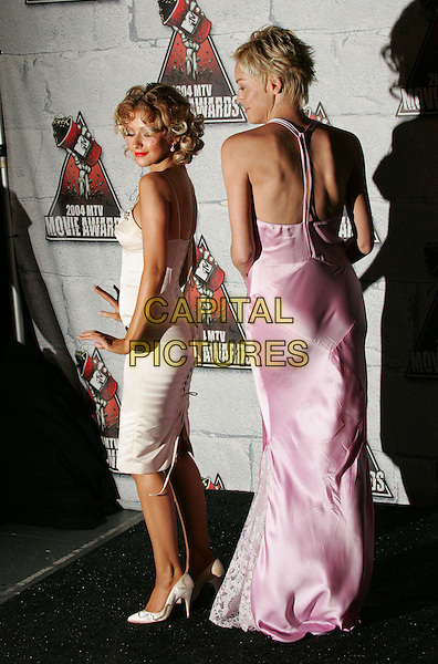 SHARON STONE & CHRISTINA AGUILERA.Attends the 2004 Mtv Movie Awards held at The Sony Picture Studios in Culver City, California  .June 6, 2004.full length, full-length, white, silk, satin dress, pink, back, behind, rear.www.capitalpictures.com.sales@capitalpictures.com.©Capital Pictures