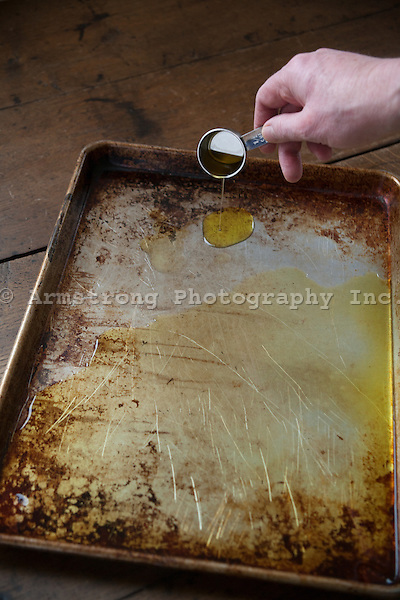 Chef's hand pouring olive oil onto a baking pan from a measuring cup.