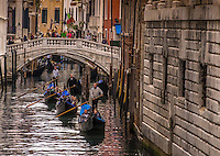 Fine Art Urban Photograph of three Gondoliers paddling down one of the romantic canals in Venice Italy.