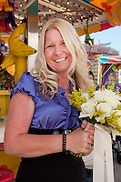 Bridjett Wood, Cape Coral, poses before exchanging wedding vows underneath the Ferris Wheel during the Collier County Fair, Naples, Florida, USA, March 26, 2011. Photo by Debi Pittman Wilkey