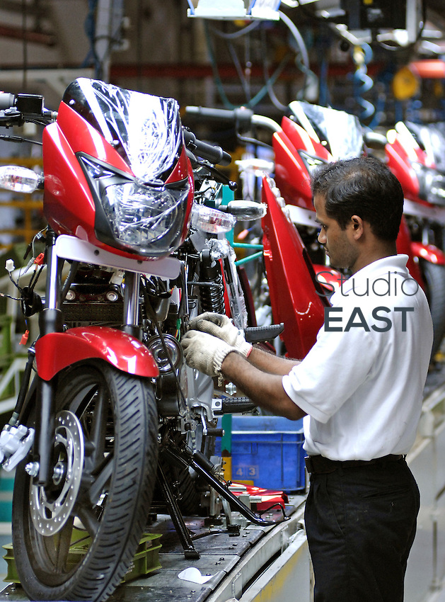 A Bajaj Auto Ltd worker gives the finishing touches to a Bajaj Pulsar motor bike on the assembly line at the company's factory in Chakan, near Pune, about 150 km East of Mumbai, India, on Thursday, August 9, 2007. French car maker Renault and India's second largest two-wheeler maker Bajaj Auto, are mulling a joint venture to make a new $3,000 car in India. Photo by Abhijit Bhatlekar/Pictobank