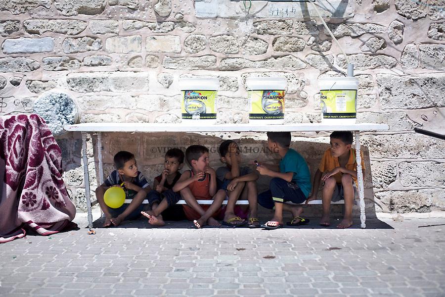 GAZA: Young refugees boys are staying under a table in the courtyard of Saint  Porphyrios Church in order to avoid the sun. <br /> <br /> GAZA: des jeunes r&eacute;fugi&eacute;s  restent sous une table dans la cour de l'&eacute;glise Saint Porphyrios afin d'&eacute;viter le soleil.