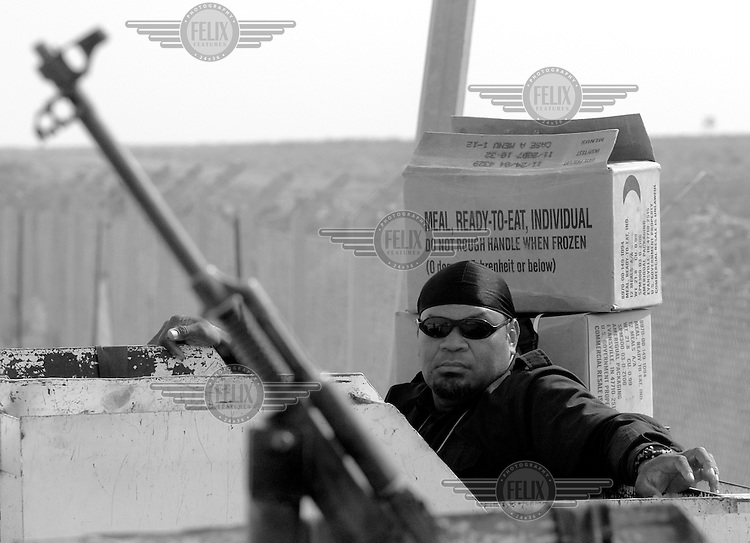 A private security operator from the British company ArmorGroup waits at a convoy staging area near Tal Afar, Iraq on October 20, 2006.  The coalition forces and civilian administration in Iraq depend heavily on thousands of controversial security contractors to support their reconstruction efforts and military operations.