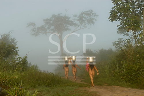 Xingu Indigenous Park, Mato Grosso State, Brazil. Aldeia Yawalapiti; thee generations of women collecting water from the river in the morning mist. This is the last time they will do this because the village now has a well, because the river water is polluted.