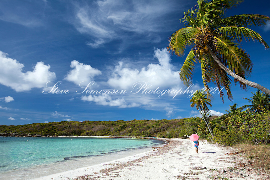 Woman with a pink parasol strolling the beach at Playa Media Luna, Vieques.Puerto Rico