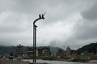 A statue of two children with damaged buildings following the 311 Tohoku Tsunami in Onagawa, Japan  © LAN