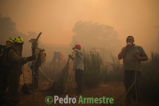 Firefighters and local residents react at the site of a wildfire in Sandin, near Ourense on August 24, 2013. (c) Pedro ARMESTRE.