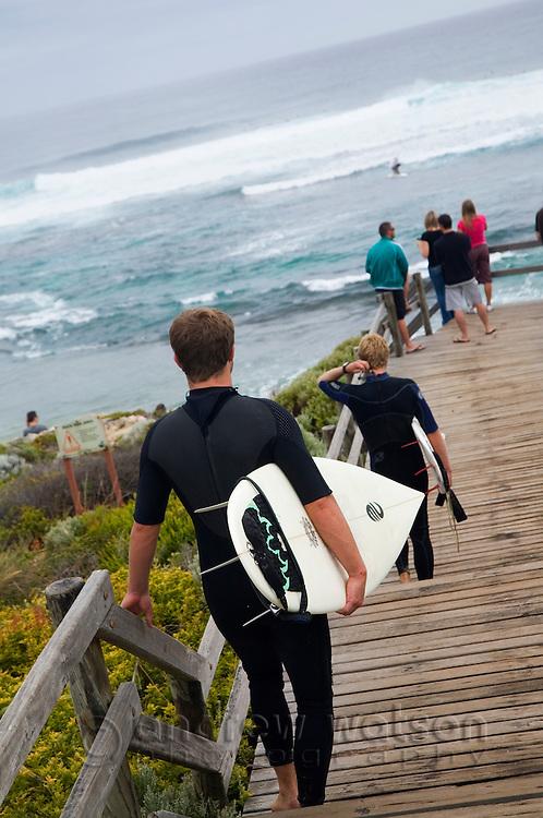 Surfers walk down to Surfer's Point, a popular break known locally as Margaret's.  Margaret River, Western Australia, AUSTRALIA.