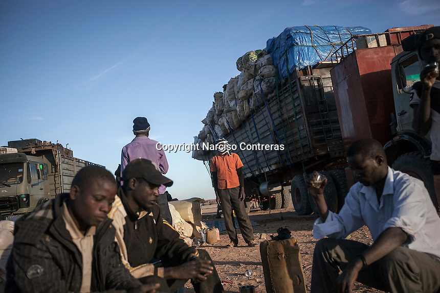 November 22, 2014 - Murzuq region, Libya: Sub-Saharan migrants are seen along trucks heavily loaded with goods at a black market area in the middle of the desert as they head to the border in Southwest Libya. Libya's revenues from smuggling trade including human trafficking is up to 10% of the national GDP, making this one of the most profitable illegal business across the country. In spite of the international concern of human rights violations, Sub-Saharan migrants risk their lives across Libya, often jailed, sold and kidnapped during their hazardous trip through the Sahara desert to the coastal ports as most of them attempt to reach Europe. (Photo/Narciso Contreras)