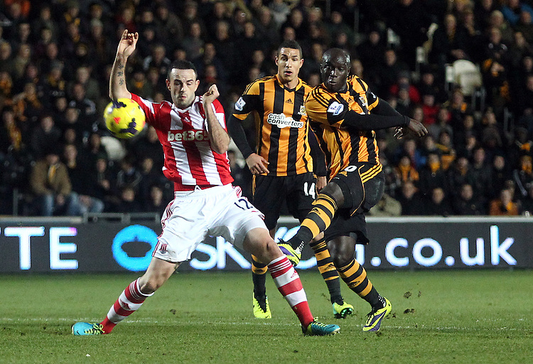 Hull City's Yannick Sagbo sends a first half strike on goal over the crossbar as he comes under pressure from Stoke City's Marc Wilson<br /> <br /> Photo by Rich Linley/CameraSport<br /> <br /> Football - Barclays Premiership - Hull City v Stoke City - Saturday 14th December 2013 - Kingston Communications Stadium - Hull <br /> <br /> &copy; CameraSport - 43 Linden Ave. Countesthorpe. Leicester. England. LE8 5PG - Tel: +44 (0) 116 277 4147 - admin@camerasport.com - www.camerasport.com