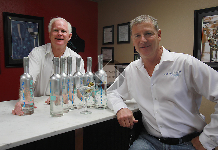 Bob Geraghty (left) and Carl Levering inside the reception room of the Mastermind Vodka distillery in Pontoon Beach.  The room resembles a high-end lounge more than a traditional reception area, complete with a bar, stools, artwork of liquor on the walls and -- plenty of their special proprietary blend Mastermind Vodka.