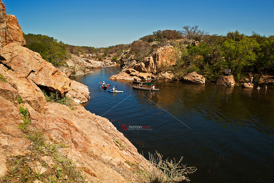 Canoers and Kayakers float along the pink granite and limestone rocks of Inks Lake State Park in the Texas Hill Country