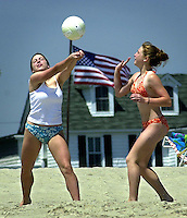 Julie Berardi, left, 16, and her sister Katelyn Berardi, right, 13, play volleyball on the beach at the start of the Memorial Day weekend, Friday, May 24, 2002, in Cape May, N.J. (Photo by William Thomas Cain/photodx.com)