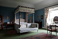 A finely carved four-poster bed in the chinoiserie style is adorned with floral bed hangings