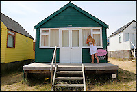 BNPS.co.uk (01202 558833)<br /> Pic: CorinMesser/BournemouthEcho/BNPS<br /> <br /> An onlooker looks into the Mudeford Spit beach hut. <br /> <br /> Britain's most expensive beach hut has gone on the market for a whopping 225,000 pounds - and it doesn't even come with sea views.<br /> <br /> The wooden shack, that measures 13ft by 13ft, looks out onto sand dunes and offers  glimpses of the sea. It is also right next to a public toilet block.<br /> <br /> The timber hut on Mudeford Spit near Christchurch, Dorset, is divided up into three rooms - a living area, bedroom and a mezzanine level.<br /> <br /> It has no bathroom, mains electricity or running water and requires a ride on a novelty land train or a 30 minute walk to get there.
