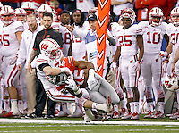 Wisconsin Badgers safety Michael Caputo (7) tackles Ohio State Buckeyes running back Ezekiel Elliott (15) during the 1st quarter in the 2014 Big Ten Football Championship Game at Lucas Oil Stadium in Indianapolis, Ind. on December 6, 2014.  (Dispatch photo by Kyle Robertson)