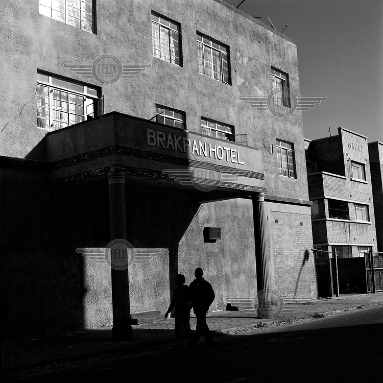 A couple walk past the Brakpan Hotel on Prince George Avenue.