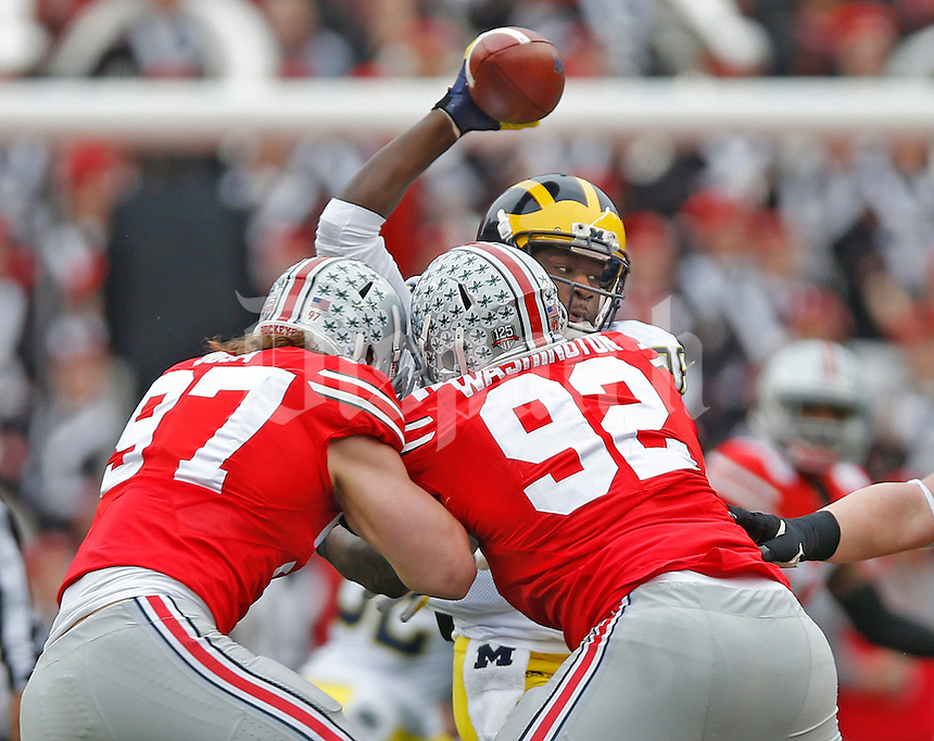 Ohio State Buckeyes defensive lineman Joey Bosa (97) and Ohio State Buckeyes defensive lineman Adolphus Washington (92) converge on Michigan Wolverines quarterback Devin Gardner (98) in first half action at Ohio Stadium on November 29, 2014. (Chris Russell/Dispatch Photo)