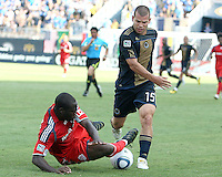 Alejandro Moreno #15 of the Philadelphia Union is tackled by Nana Attakora #3 of Toronto FC during an MLS match at PPL stadium in Chester, PA. on July 17 2010. Union won 2-1 with a last minute penalty kick goal.