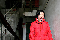 11 year old Liu Fangyuan(Yuan Yuan) stands in the stairwell where an attack destroyed her face out side her family's apartment in Nanjing, China. In 2002, Yuan Yuan's aunt poured sulfuric acid on her face after losing a housing dispute with Yuan Yuan's father in regards to a 40 squared meter apartment. The attack blinded and seriously disfigured Yuan Yuan, while her aunt is serving a life sentence in prison, Yuan Yuan and her family awaits a controversial face transplant...PHOTO BY SHEN / SINOPIX