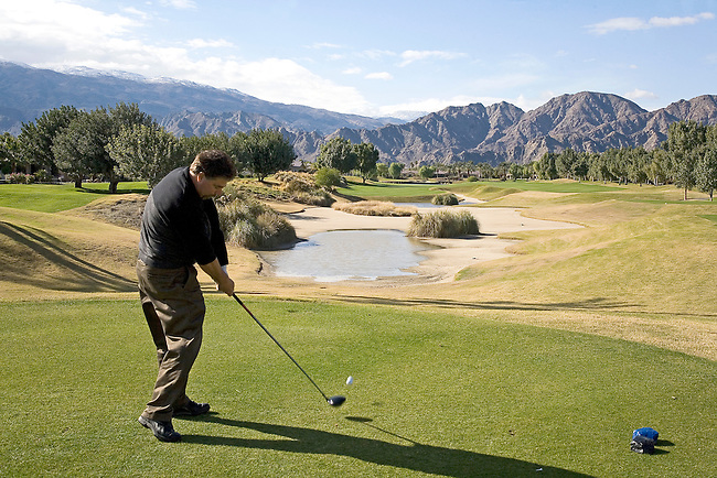 GOLFER TEEING OFF AT PALM SPRINGS AREA GOLF COURSE