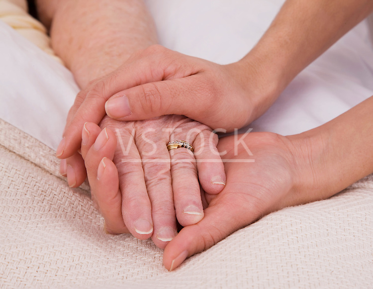 Woman holding senior woman's hand on bed, close-up