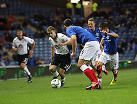 Danny Carmichael runs at Lee Wallace as he is tracked by Ian Black in the Rangers v Queen of the South Quarter Final match in the Ramsdens Cup played at Ibrox Stadium, Glasgow on 18.9.12.