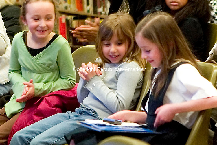 WATERBURY, CT- 10 APRIL 07- 041007JT07- <br /> Jacquelynn DeSantis and Colleen Flanagan look at first grader Elena Tormo's first prize award for the annual poetry contest at Silas Bronson Library on Tuesday evening in Waterbury. <br /> Josalee Thrift Republican-American