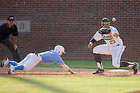 Levi Michael #1 of the North Carolina Tar Heels dives head first into first base as David Anderson #23 of the Coastal Carolina Chanticleers waits for the ball at Boshamer Stadium May 30, 2010, in Chapel Hill, North Carolina.  Photo by Brian Westerholt / Four Seam Images