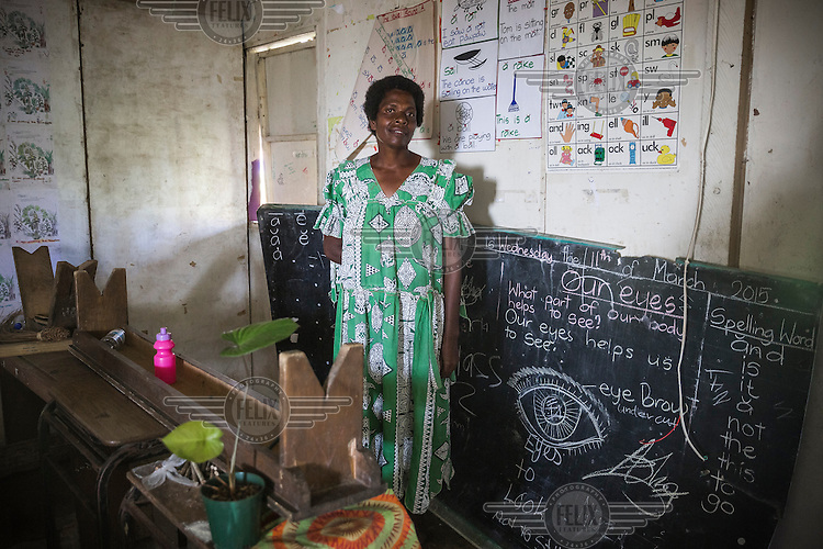 Ambito Valia (45), a teacher of maths and science in grades 7-8 stands among items rescued from the school following the destruction wrought by Cyclone Pam on 13 March 2015. She says: 'Our school roof is damaged, many books were washed out. Student's desks and blackboards were damaged. School has not operated for two weeks. We are supposed to start classes next week, but I'm not sure if this will happen. The damage hasn't been repaired.'