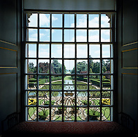View through a window over an ornamental lake and the manicured gardens beyond