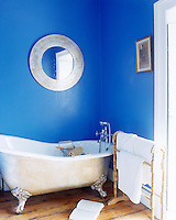 In the fresh blue-and-white bathroom a round white-framed mirror hangs above the traditional ball-and-clawfoot bath
