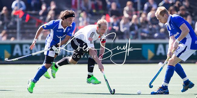 AMSTELVEEN -  Billy Bakker (A'dam) tussen Pepijn Luijkx (l)  van Kampong en Erik Bouwens van Kampong  tijdens de 3e en beslissende  halve finalewedstrijd in de Play offs tussen Amsterdam en  Kampong (3-1) .  COPYRIGHT KOEN SUYK