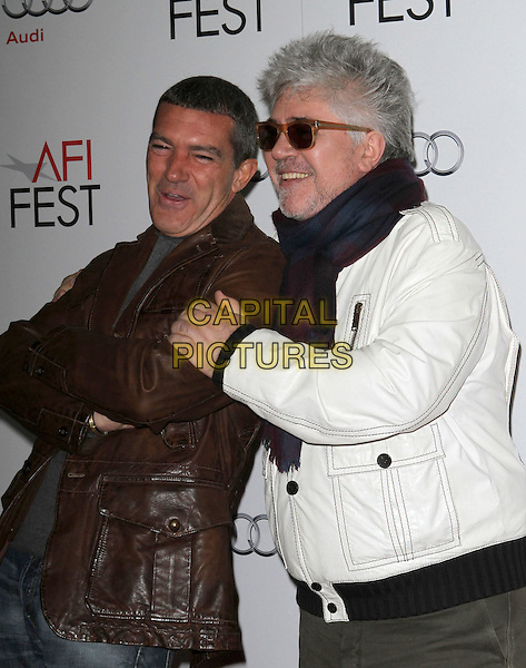 "Antonio Banderas & Pedro Almodovar.AFI Fest 2011 premiere of ""Law Of Desire/ An Evening with Pedro Almodovar Tribute"" held at Grauman's Chinese Theatre, Hollywood, California, USA..November 7th, 2011.half length jacket top jeans denim brown leather grey gray white sunglasses shades smiling scarf black arms crossed .CAP/ADM/KB.©Kevan Brooks/AdMedia/Capital Pictures."