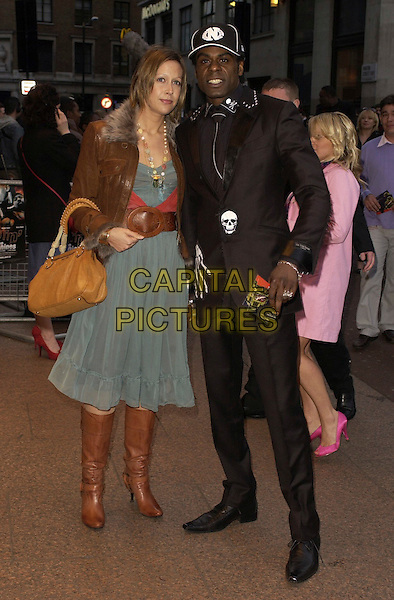 """NORMSKI & GUEST.""""Rollin' With The Nines"""" - UK premiere at the Odeon Leicester Square, London, UK..April 19th, 2006.Ref: CAN.full length black trousers suit jacket baseball cap hat green dress brown boots leather jacket purse.www.capitalpictures.com.sales@capitalpictures.com.©Capital Pictures"""