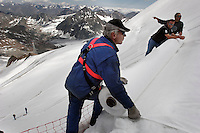 Workers prepare to unroll uncovered fleece-like material and attached it to the top of the part of the glacier. Brunnenkogel Ferner (Austrian word for glacier) is wrapped with a cover to keep it from melting.   Covered ice melts slower. <br /> The ski area at 3,400 meters is covered to help save the ski industry since the glacier is retreating.  The cost of materials is one Euro per square meter.<br /> <br /> The Alpine glaciers -- in Austria, Switzerland, France and Italy -- are losing one percent of their mass every year and, even supposing no acceleration in that rate, will have all but disappeared by the end of the century. More hot, dry summers like that of 2003 in Europe, when the loss speeded to five percent, could cut the life expectancy to no more than 50 years, according to Wilfried Haeberli of the University of Zurich...&quot;We estimate that by the end of the 21st century, with a medium-type climate scenario, about five percent of what existed in the 1970s will have survived, he added.