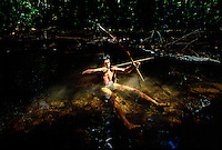An Amerindian hunter hits silently aiming at a bird while hunting in the jungle.