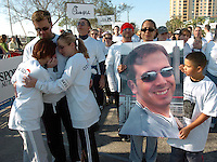Hillsborough, Tampa, Fl. 2/5/2005--GASPARILLARUN -- Ciana Hamilton (mom, left) Jennifer Lyons (sister) Tim Hill (console each other as they cross the finish line during the Bank of America Distance Classic 15k along Bayshore Blvd. Holding the photo is Elizabeth Colon and Anthony Colon. PHOTOS 2 OF IMAGES STAFF MS