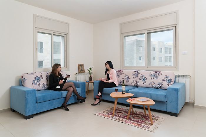 "April 2018. Muna, 27 (on the left) and her new flatmate Sawsan, 33 (on the right). The two women work in the ""Q center"", the open air mall located at the heart of the city, and live in rented apartment. The two women, who present themselves as ambitious and independent woman know each-other from university. Muna says she appreciate that women can find opportunities in Rawabi. Their work represent most of their life occupation, there is no much time left out of working time, only to appreciate a glass of wine after a working day."