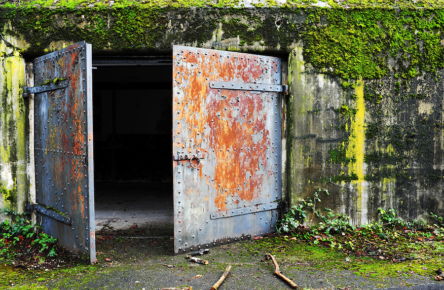 Open rusty steel door at concrete bunker tunnel, Artillery Hill, Fort Worden State Park, Port Townsend, Washington, USA