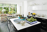 A spacious open plan kitchen diner with black and white units and a black slate floor. A light wood table and chairs are placed at the end of the kitchen island, which has a Corian worktop.
